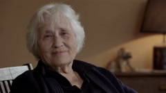 Quiet and relaxed old lady smiling at the camera Stock Footage