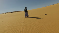 Nubian man wearing traditional clothing standing in sandy desert. Stock Footage