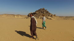 Nubian man wearing traditional clothing walking in desert with tourist. Stock Footage