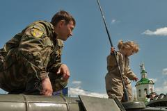 Policeman and little girl on armoured carrier - stock photo