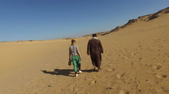 Back view of nubian man walking in desert with female tourist. Stock Footage