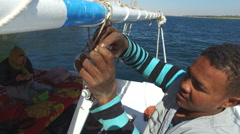 Crew member unwinding rope on felucca boat Stock Footage