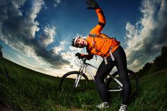 Man Cyclist with bike on sunset - stock photo