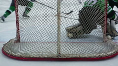 View from behind net, hockey goaltender repulsing violent attack, catching puck Stock Footage