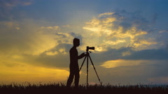 The man work with the camera on the background of sunset. Time lapse Stock Footage