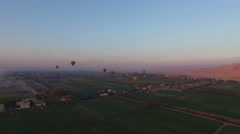 Hot air balloons flying over the fields in Luxor at sunrise Stock Footage