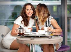 Girl friends in the a cafe gossip - stock photo
