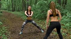 Two slender fitness girl in the forest. Brunettes practice exercises on the path Stock Footage