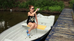 Girl sitting in a boat and making video with a cellphone Stock Footage