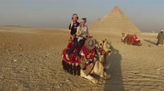 Smiling couple sitting on camel in front of Giza pyramids - stock footage