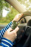 Woman driving car and reading received sms message on smartphone Kuvituskuvat