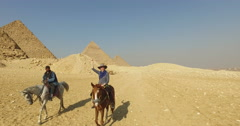Happy woman riding horse with local man in front of Giza pyramids - stock footage