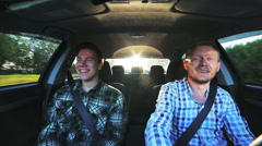 Two happy friends laughing in car while driving - stock footage
