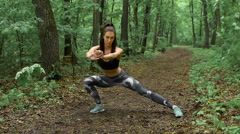 Slim fitness woman on a forest path. The brunette with long hair and performs an Stock Footage