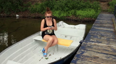 Sexy girl sitting in a boat and texting on the cellphone and waiting for someone Stock Footage