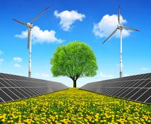Solar energy panels with wind turbines and tree on dandelion field. - stock photo