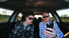 Two men in sunglasses driving in the car, using phone in the sunny day - stock footage