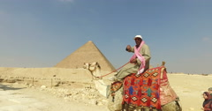 Egyptian man on a camel at Giza pyramids complex - stock footage