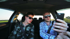 Two men driving in the car, using phone and smiling Stock Footage