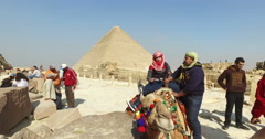Tourist on a camel in front of pyramids of Giza Stock Footage