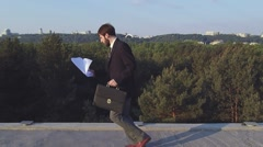 Businessman runs and throws the papers. Shooting with quadrocopter Stock Footage