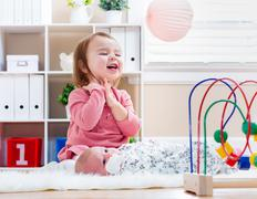 Happy toddler girl playing with her baby sibling Stock Photos