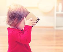 Toddler girl with virtual reality headset - stock photo