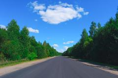 Empty highway, green forest and clouds - stock photo