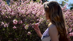 Young girl smelling a pink little flowers Stock Footage