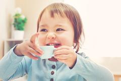 Happy toddler girl drinking from a teacup - stock photo