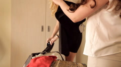 Young girls at home put clothes in a suitcase for vacation Stock Footage