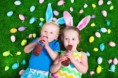 Kids eating chocolate rabbit on Easter egg hunt - stock photo