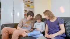 little boy playing portable game console. the family watching him with interest - stock footage