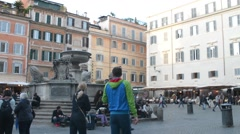 Rome, Italy. Fountaine on piazza Trastevere. Tourists relax, eating, walking. Stock Footage