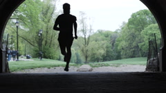 Silhouette of a man running running through a park in slow motion Stock Footage