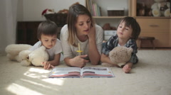 Young mother, read a book to her tho children, boys, in the living room Stock Footage