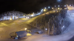 Flying over ski slopes and working lift at night - stock footage