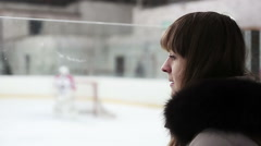 Young woman watching hockey match, worried about score and players on ice rink Stock Footage