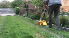 Old man cutting the grass with electric lawn mower Stock Footage