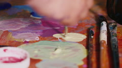 The artist mixes paint on the palette. In the picture is only visible hand Stock Footage