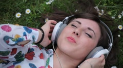 Beautiful Girl Listening to Music in a Daisy Meadow Stock Footage