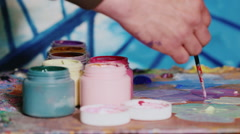 The artist is preparing the paint. Brush paint mixes and selects the desired Stock Footage