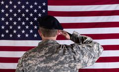 Veteran solider saluting the flag of USA flag - stock photo