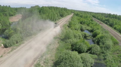 Flying over military vehicle on dirt road in woodland Stock Footage