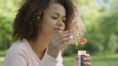 Beautiful woman blowing bubbles in sunny park. - stock footage