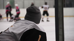 Disqualified or injured hockey team player watching match on ice rink from bench Stock Footage