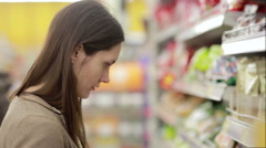Girl selects the item on the shelves in the store Stock Footage