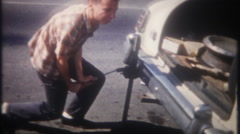 Teenager changes flat tire and back on the road - 3324 vintage film home movie Stock Footage