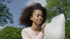 Beautiful afro woman with candy floss in sunny park. Stock Footage