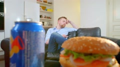 Man watch TV and take hamburger and cola at home Stock Footage